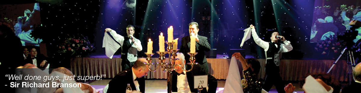 Three waiters performing, candle on the foreground, gentlemen dining